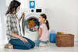 Leinwandbild Motiv daughter in pink t-shirt and mother in grey shirt sitting on floor near washer with clothes in laundry room