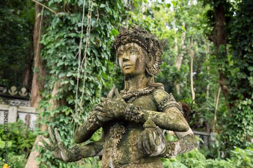 Stone idol of multiarm god in Bali, Indonesia.