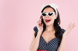 Attractive brunette woman in sunglasses talking on smartphone isolated on pink