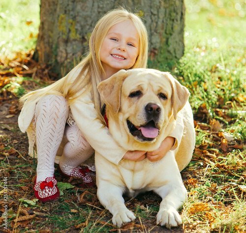 Leinwandbild Motiv Cute little blonde girl sitting with dog on the grass in the forest