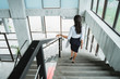 portrait from behind of businesswoman walking down stairs alone in the office