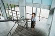 portrait of businesswoman walking up stairs alone in the office