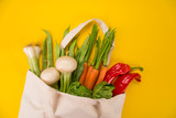 Fresh vegetables in bio eco cotton bags on yellow background. Zero waste shopping concept. Plastic free.