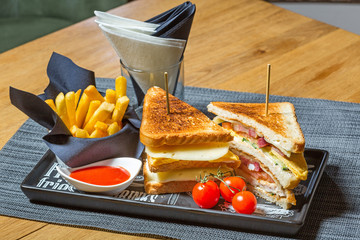 Club sandwich with cheese, cucmber, tomato and smoked meat. Garnished with French fries