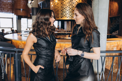 Two stylish sexy glamour elegant women wear black latex dress in a restaurant. Party and birthday time.