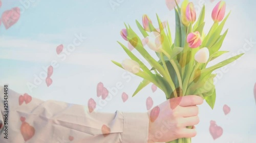Mid-section of a man holding a bouquet of tulips with a blue sky background