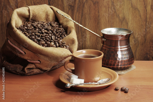 A cup of coffee, a coffee grinder, a bag of coffee on a wooden table.