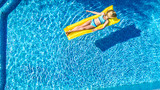 Girl relaxing in swimming pool, child swims on inflatable mattress and has fun in water on family vacation, tropical holiday resort, aerial drone view from above