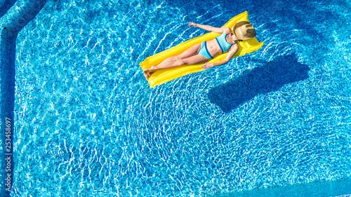 Leinwandbild Motiv Girl relaxing in swimming pool, child swims on inflatable mattress and has fun in water on family vacation, tropical holiday resort, aerial drone view from above