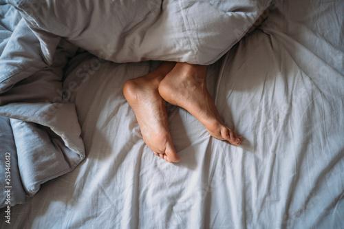 Leinwandbild Motiv Close-up woman feet alone in white bed