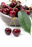 Steel colander with red sweet cherry isolated on a white background..