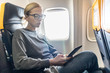 Blonde casual caucasian woman wearing glasses reading on digital e-reader while traveling by airplane. Commercial transportation by planes.