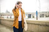 Cute girl listening music white walking in the street