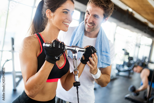 Leinwanddruck Bild Young beautiful woman doing exercises with personal trainer