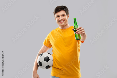 sport, leisure games and people - happy man or football fan in yellow t-shirt with soccer ball and beer bottle over grey background