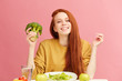 Young beautiful happy attractive female with gorgeous long ginger hair having dinner with fresh broccoli and vegetables at table, isolated over pink background. Healthy diet concept. Vegetarian food - 253495625