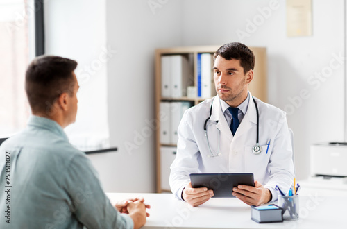 medicine, healthcare and technology concept - doctor with tablet pc computer and male patient talking at medical office in hospital - 253501027