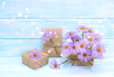 Chamomile flowers and gift box on wooden background in Shabby Chic style.