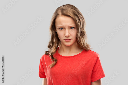emotion, expression and people concept - sad or angry teenage girl in red t-shirt over grey background