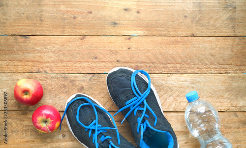 Getting fit and reducing weight, pair of sports shoes, apples bottle of water,concept,free copy space,flat lay