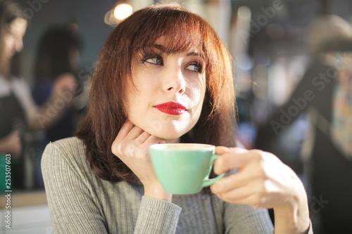 Beautiful woman drinking coffee in a bar - 253507603