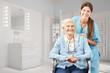 Leinwanddruck Bild - Seniorin und Krankenpfleger im Bad als Pflegedienst Konzept