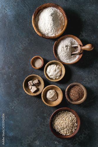 Ingredients for baking bread. Variety of wheat and rye flour, grains, yeast, sourdough over dark blue texture background. Flat lay, space