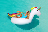 Sexy girl sunglasses having fun in the pool floating on a large inflatable unicorn in a hotel on summer vacation on a tropical island. The concept of summer leisure freedom of pleasure