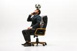 Biznesmen z futbolową piłką w biurze. Piłka nożna freestyle. Pojęcie równowagi i zwinności w biznesie. Kierownik perfoming triki siedząc na krześle i mówiąc na smartfonie na białym