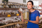 adult  female take a smell natural dried herbs sold by weight in eco shop