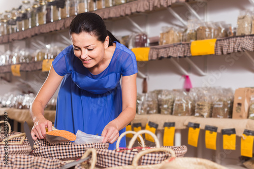 woman taking dried beans with shovel from backet in organic shop