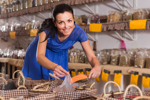 female customer  taking сereals with scoop from basket in eco market