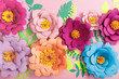 top view of paper colorful flowers and leaves on pink background