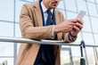 cropped view of businessman using smartphone while standing in beige coat
