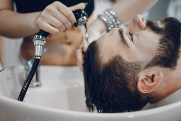 handsome young bearded guy sitting in an armchair in a beauty salon and the girl near  him washes his head under the jet of water