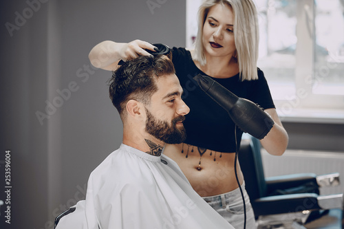 handsome young bearded guy sitting in an armchair in a beauty salon and the girl around him dry his hair