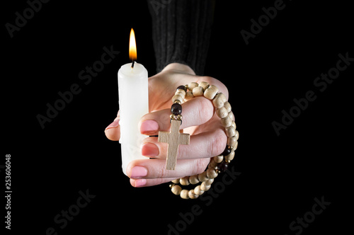 Woman's hand holding burning candle and wooden rosary beads on black.