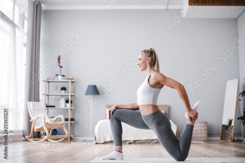 Leinwanddruck Bild Sporty beautiful woman stretching exercising at home.