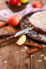 homemade apple pie - on a plate with fresh apples and cinnamon sticks on a rustic wooden table