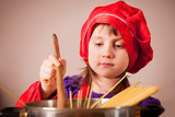 Little cute child girl chef cooking a meal stirring the contents of the pot.  Cooking process and food concept.