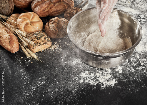 Baker dusting his dough with flour from his hands
