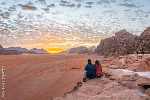 Leinwandbild Motiv A young couple is watching at sunrise over wadi rum desert in Jordan