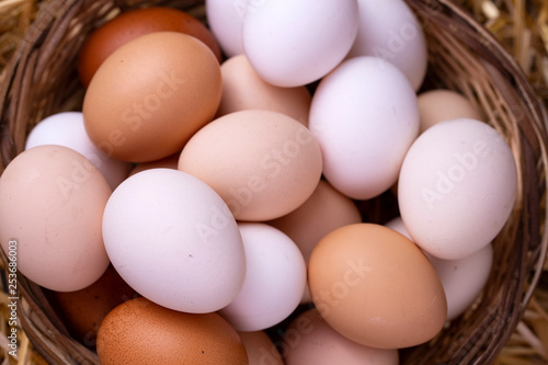 Raw eggs in dry straw. Food concept photo.
