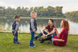 Leinwanddruck Bild - Family and nature concept - Mother, father and their children playing with colorful soap bubbles