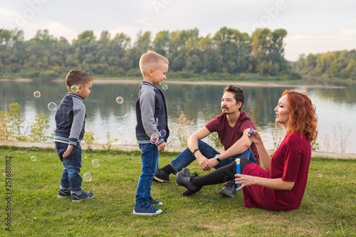 Leinwanddruck Bild Family and nature concept - Mother, father and their children playing with colorful soap bubbles