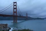 Golden gate bridge on dark, cloudy day with hills in background