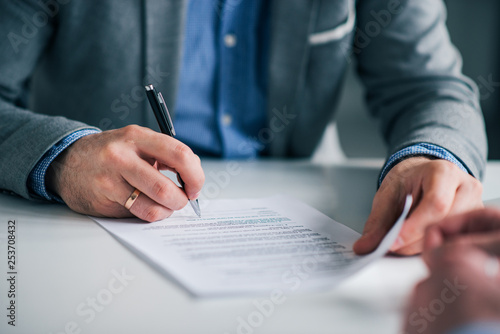 Leinwanddruck Bild Businessman sitting at desk holding and pen signing contract paper, employment or partnership agreement.