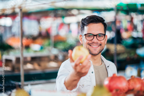 Handsome young man holding apple toward camera at farmer's market.