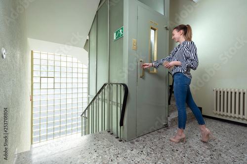 obraz lub plakat Arbeitswelt im Wandel der Zeit, junge Frau im Treppenhaus eines alten Bürogebäudes am Aufzug stehend