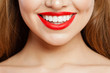 Red makeup Lips with trendy color tint lipstick. Beautiful female smile and perfect white teeth
